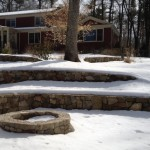 Natural stone fire pit nestled into curve in the wall.  Waiting for spring.